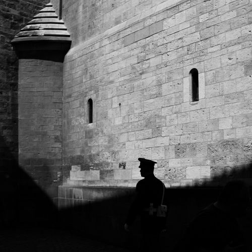 View of policeman against sun lighted wall