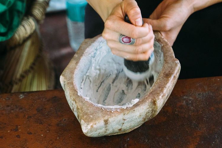 Close-Up Of Woman Mortar And Pestle While Preparing Food At Table