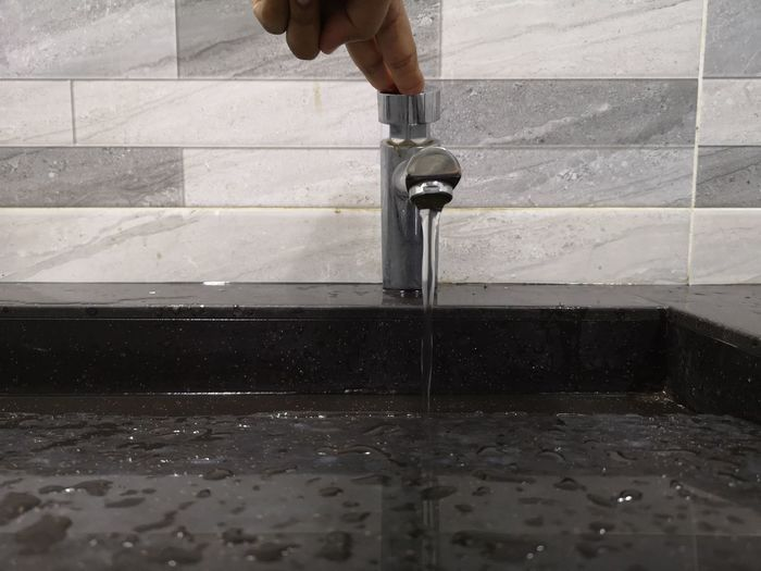 Cropped hand touching faucet