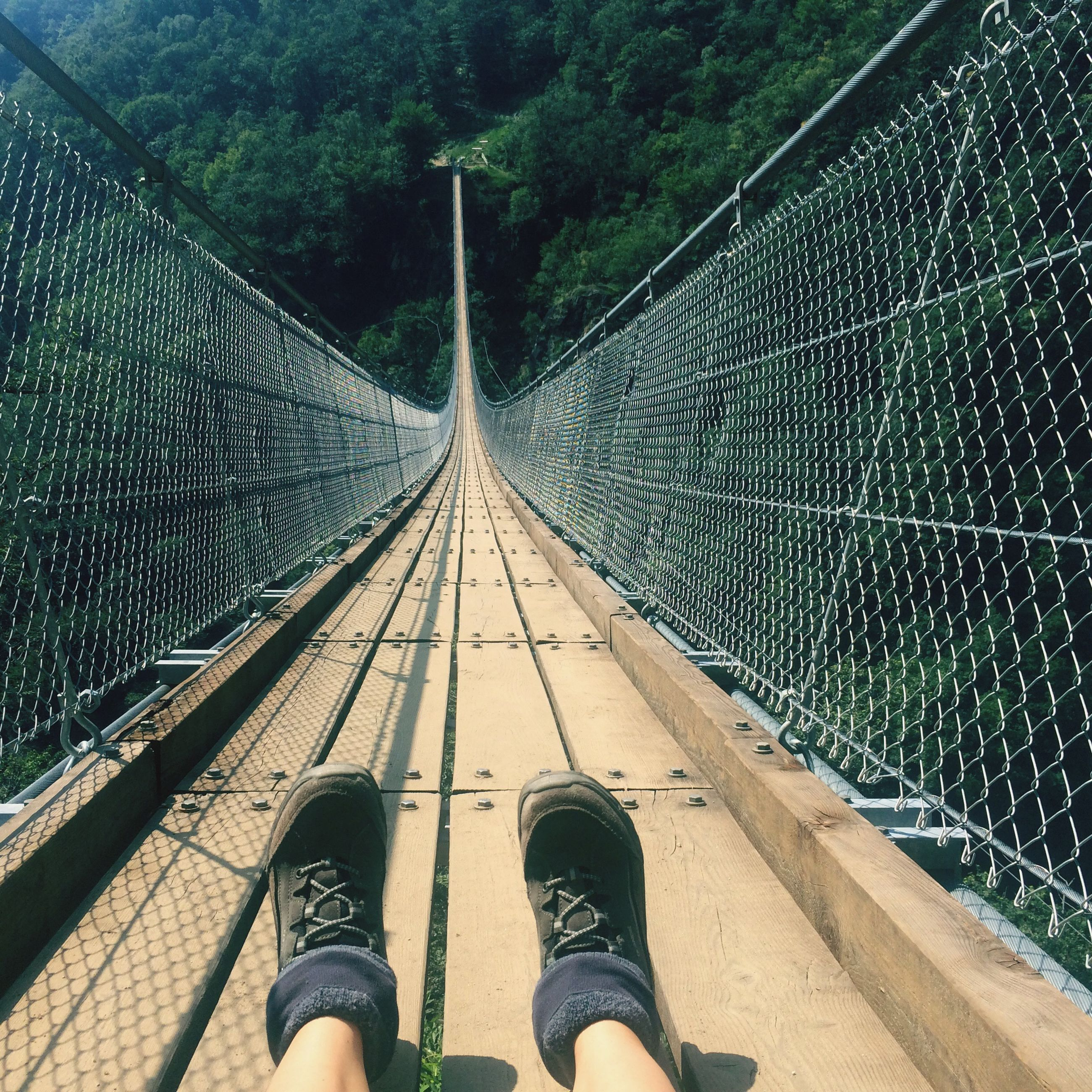 low section, person, the way forward, personal perspective, railing, lifestyles, standing, diminishing perspective, men, leisure activity, metal, footbridge, unrecognizable person, connection, bridge - man made structure, shoe, vanishing point