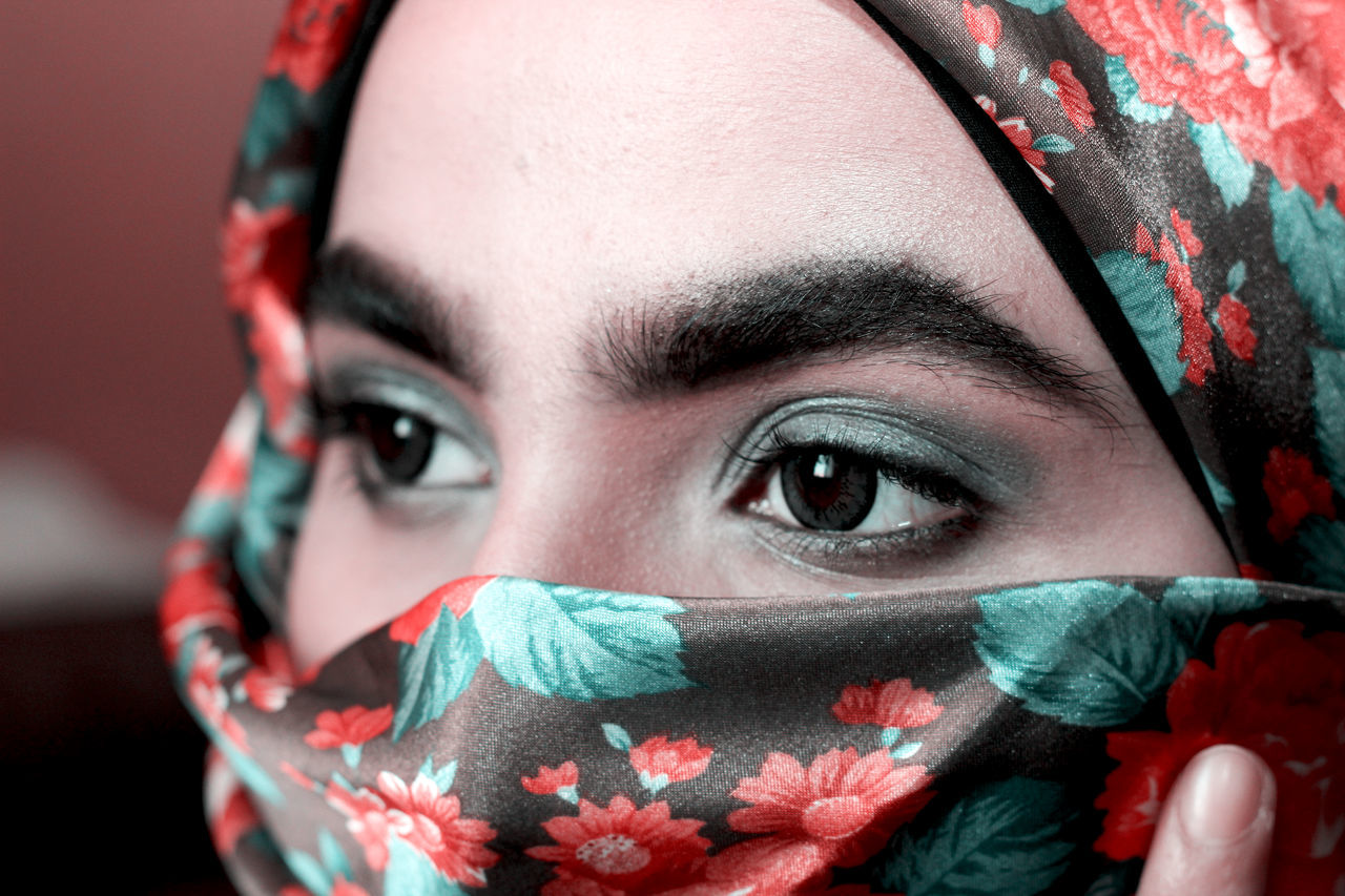 Close-up of woman with gray eye shadow wearing headscarf