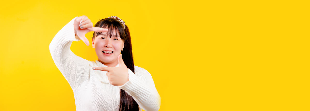 Portrait of smiling young woman standing against yellow background