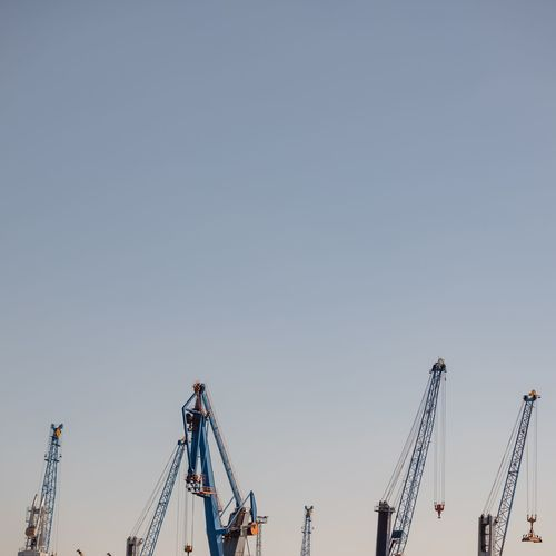 Cranes at construction site against clear sky