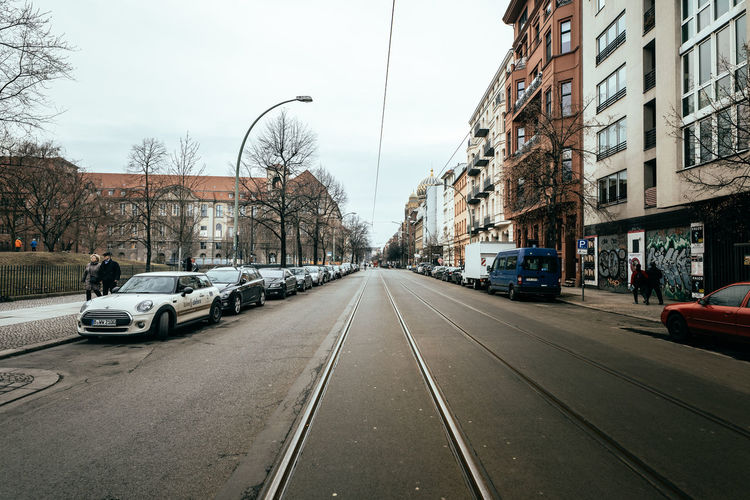 Cars on street in city against clear sky