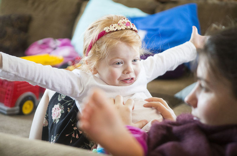 A three-year-old redhead toddler tries to scare her sister with a funny face. Baby Bonding Boo Crown Daughter Excitement Females Funny Faces Happiness People Playing Princess Redhead Smiling Suprised Surprise Tadaa Toddler  Togetherness Two People