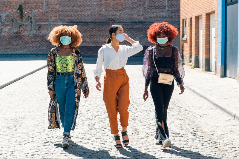 Female people walking in the street with protective mask - friends with surgical mask protection