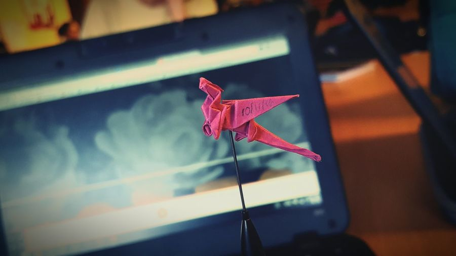 Close-up of red dragon origami against laptop