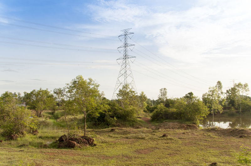 Electricity Pylon On Countryside Landscape Against Sky