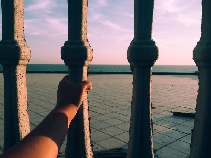 Close-up of hand holding railing against sea at sunset