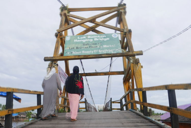 Adventure Beauty In Nature Bridge Day Full Length Leisure Activity Lifestyles Lok Baintan Bri Men Nature One Person Outdoors People Railing Real People Rear View Sky Standing Walking Women Young Adult Young Women