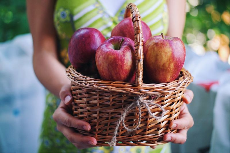Close-up of woman holding apple in basket
