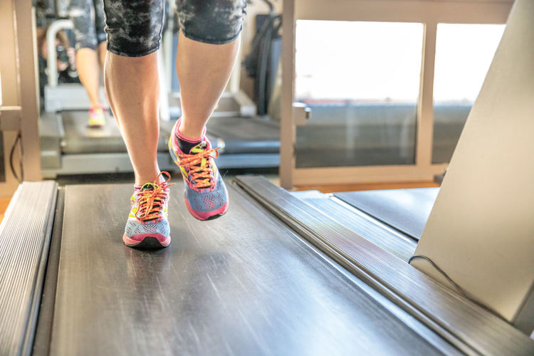 Low Section Of Person Running On Treadmill In Gym