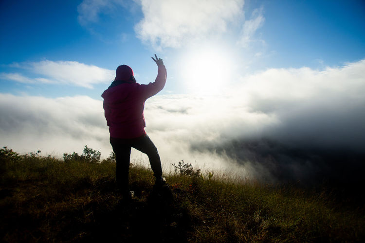 Rear view of woman with arms raised gesturing peace sign while standing on field against sky
