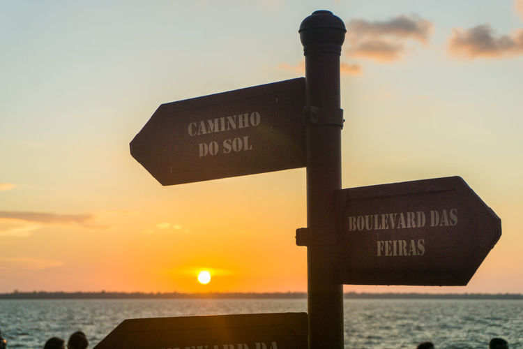 Sunset Direction Arrow Symbol Guidance Discovery Sky Road Sign Danger No People Travel Destinations Silhouette Nature Outdoors Rural Scene Vacations Sea Day Close-up