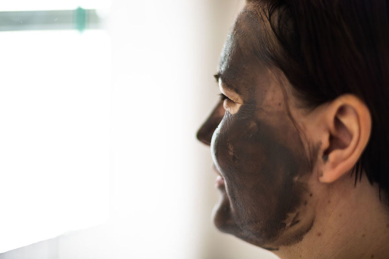 Close-Up Of Woman Wearing Facial Mask Against Wall