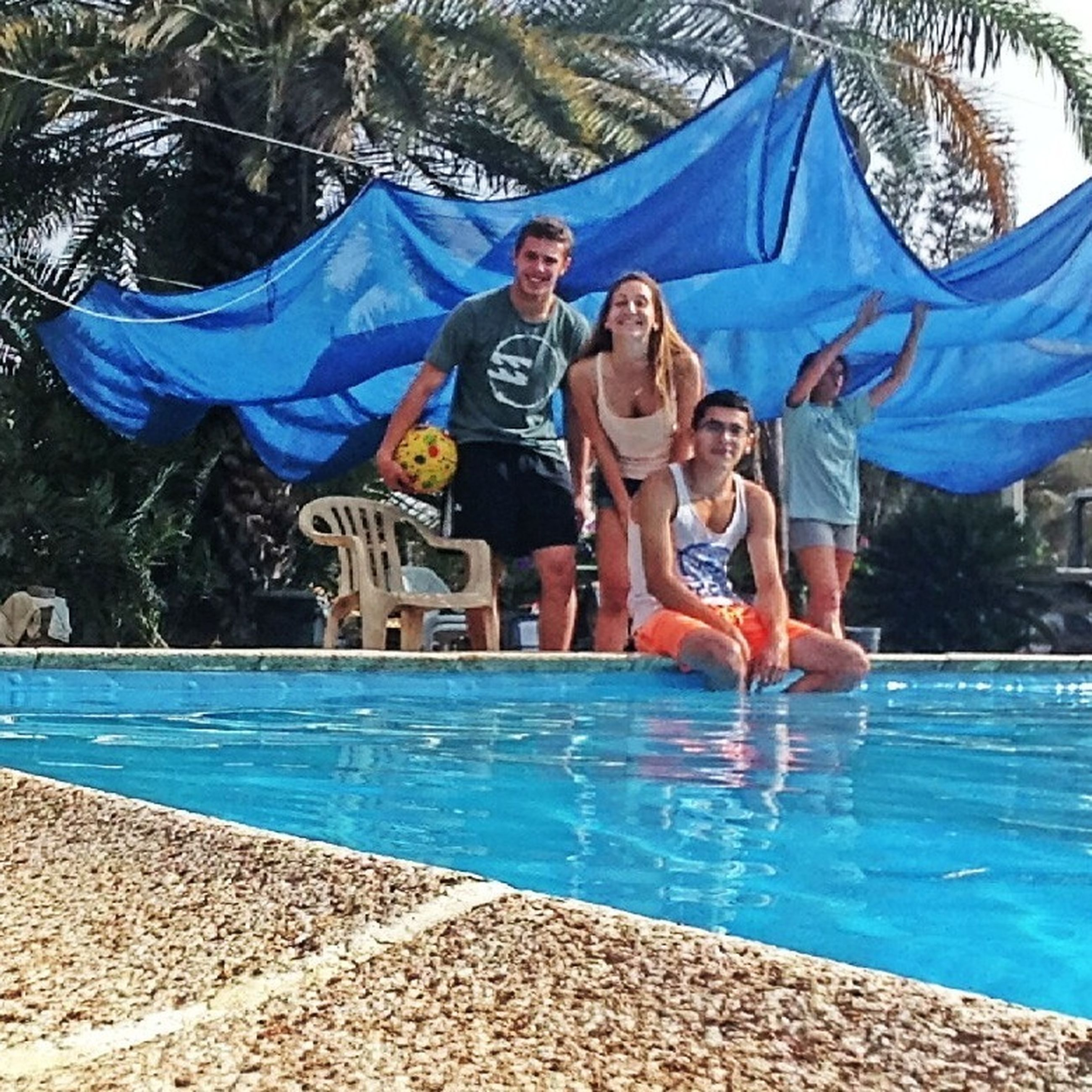 lifestyles, leisure activity, water, swimming pool, enjoyment, blue, vacations, fun, casual clothing, young adult, full length, relaxation, sitting, person, happiness, togetherness, men
