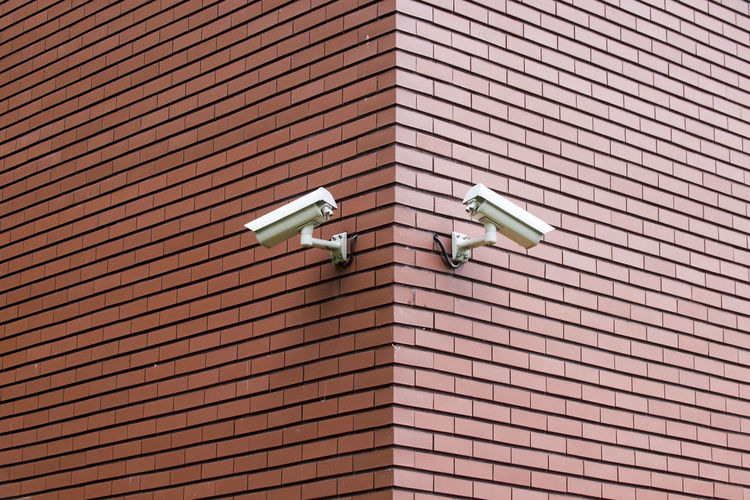 Low angle view of security camera on brick wall