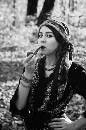 Portrait of beautiful young woman smoking pipe while sitting outdoors
