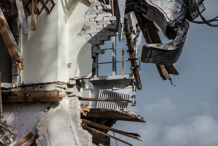 Low Angle View Of Machinery Demolishing Building Against Sky