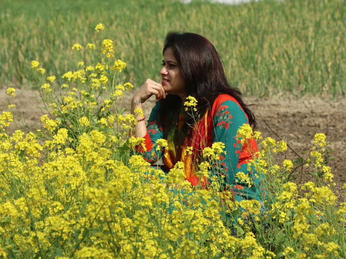 Young woman with yellow flowers on field