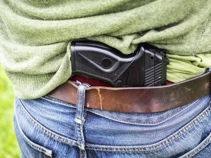 Midsection of man with pistol