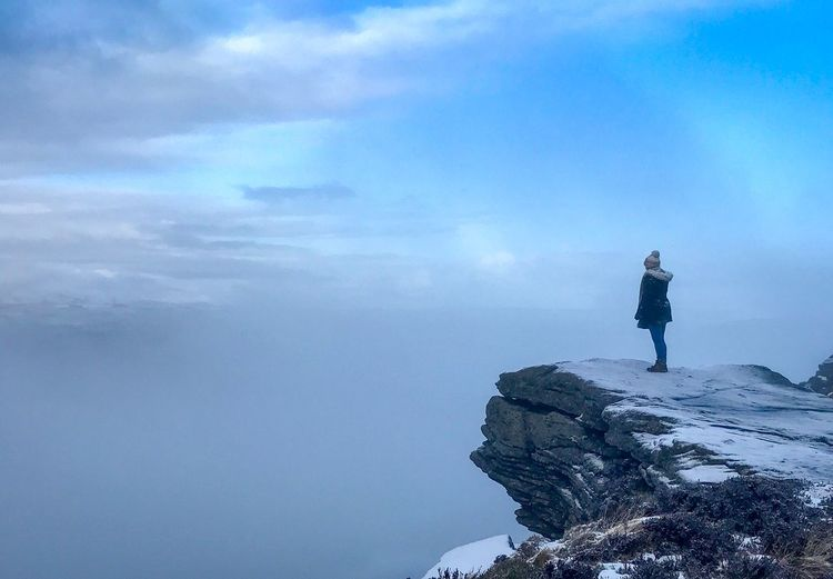 Side View Of Woman Standing On Cliff Against Cloudy Sky During Winter