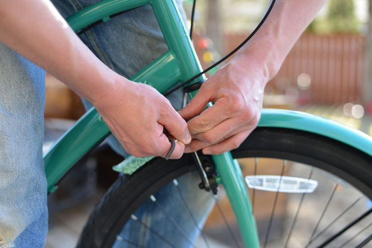 Midsection of man repairing bicycle