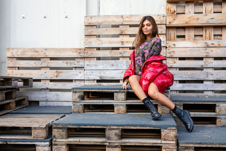 Fashionable Smiling Young Woman Sitting On Palettes