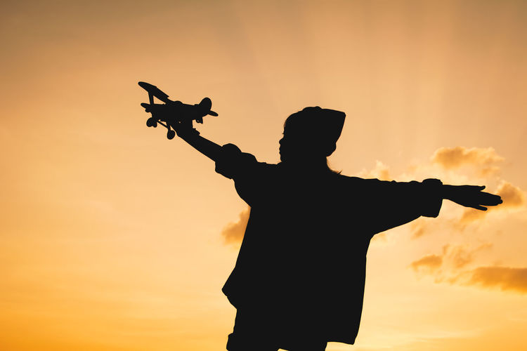 Silhouette Girl Holding Toy Airplane Against Sky During Sunset
