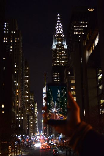 Cropped image of hand photographing chrysler building in city at night