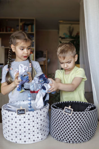 Cute sibling putting clothes in container