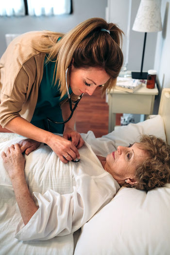 Female caregiver auscultating senior woman at home Bed Care Doctor  Hospital Nursing Woman Aged Auscultation Clinic Elderly Examining Health Care Healthcare And Medicine Heart Home Assistance Home Assistant Illness Medical Nursing Home Patient Senior Stethoscope  Treatment Two People Vertical