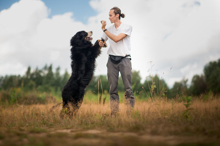 Man playing with dog while standing on grassy land against cloudy sky