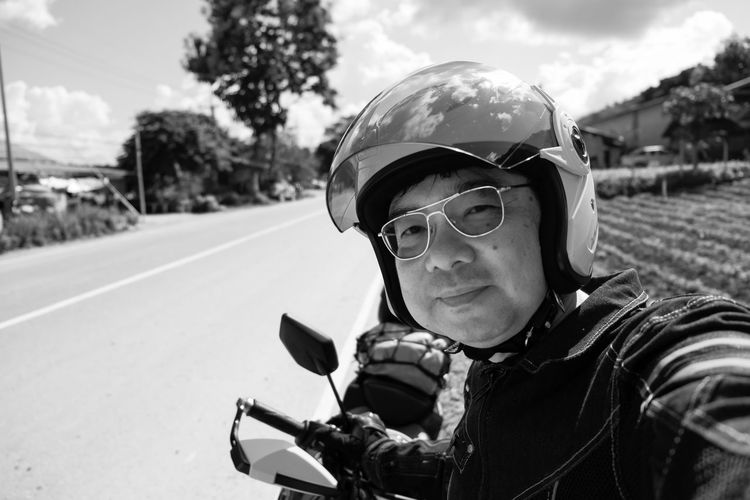 Portrait of mature man wearing helmet with motorcycle on road