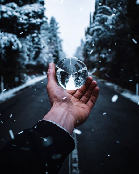 Cropped hand holding crystal ball during snowfall