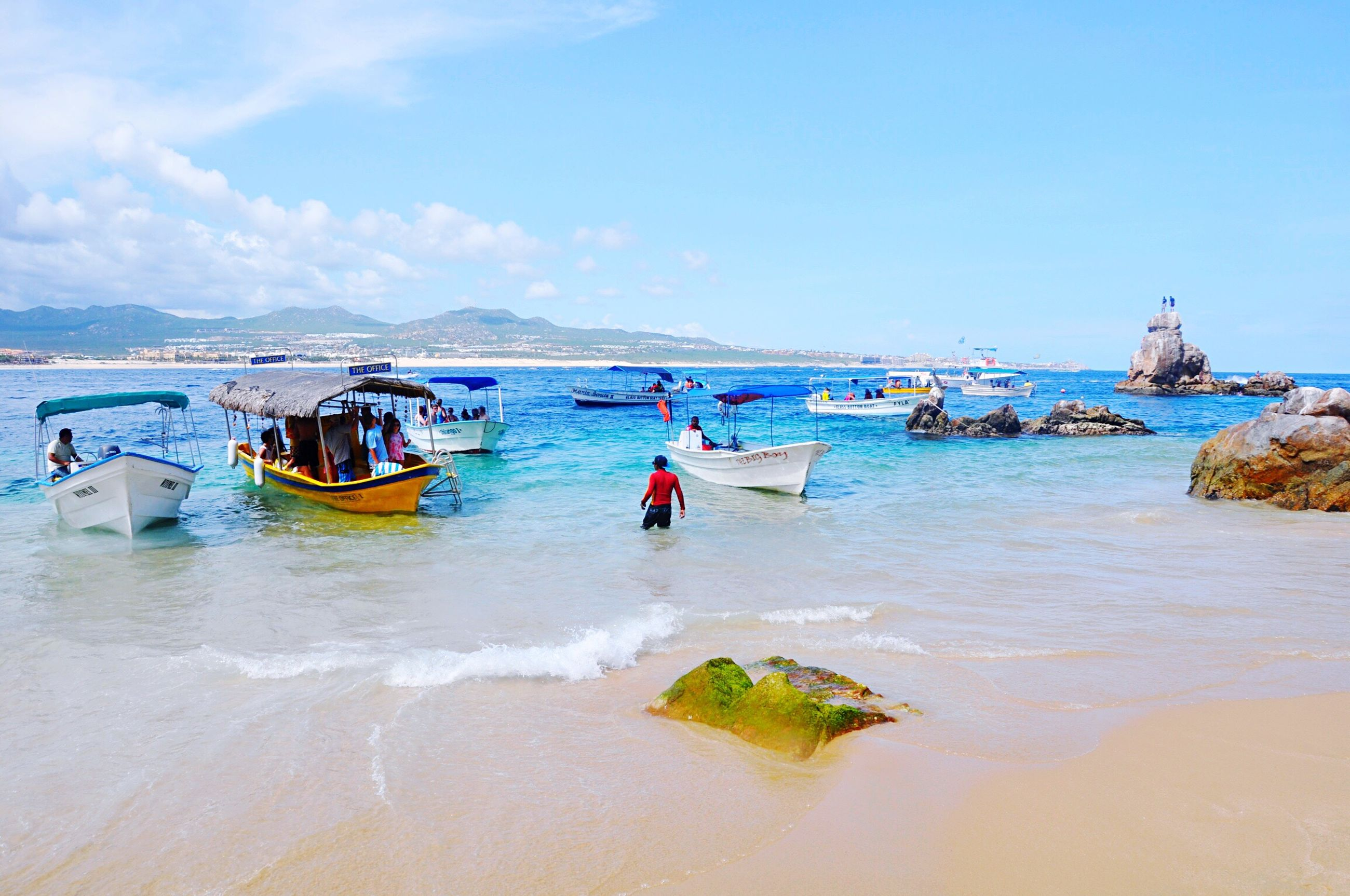 beach, water, sea, shore, transportation, moored, nautical vessel, sand, mode of transport, sky, wave, vacations, scenics, nature, outdoors, day, large group of objects, tourism, beauty in nature, tranquil scene, blue, tranquility, seascape