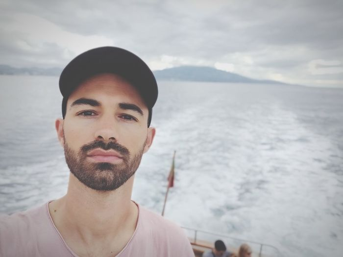 Portrait of young man in boat at sea against sky