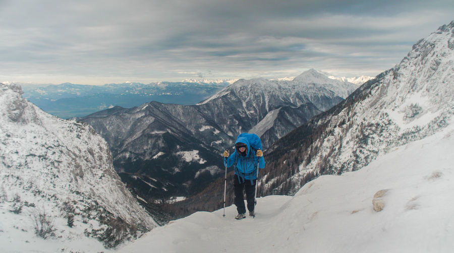 Woman Hiking Uphill On Snowcapped Mountain Against Sky