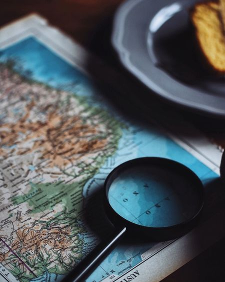 Close-up of magnifying glass on map at table