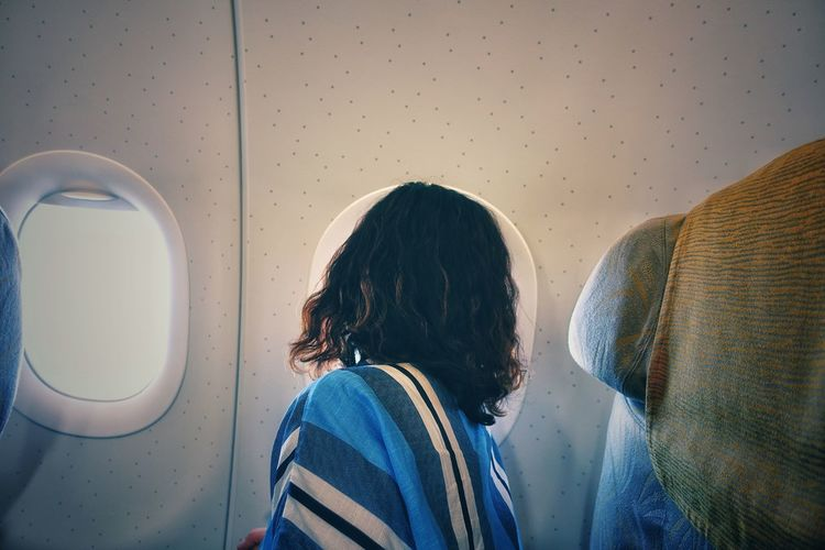 Side view of woman looking through window while traveling in airplane