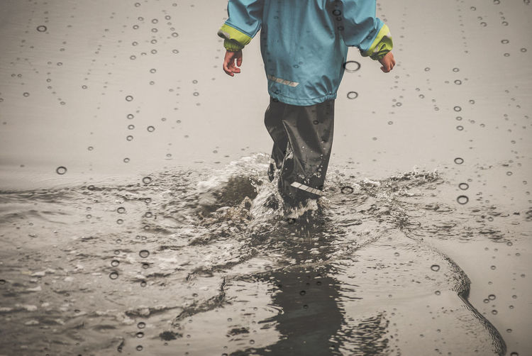 Low section of boy standing in water