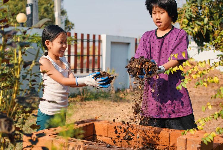 Siblings putting dirt in flowerbed