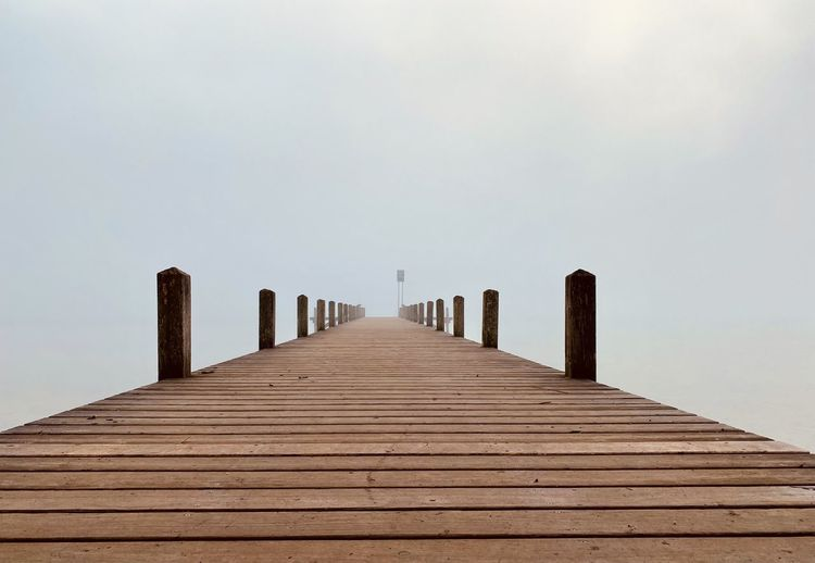 Wooden jetty leading to sea against clear sky