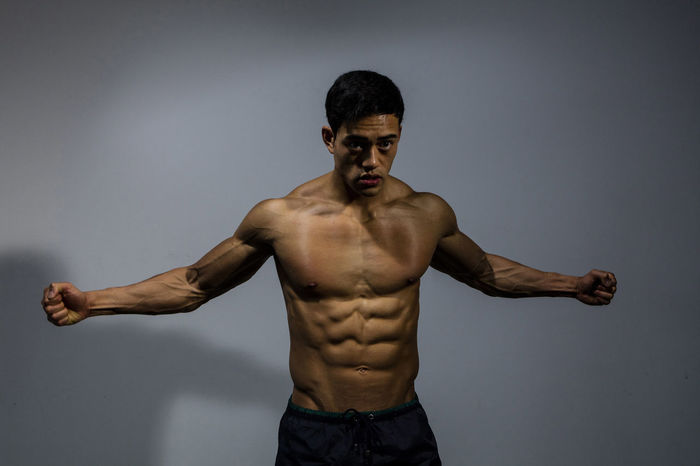 Male fitness model displays his muscular physique by spreading out his arms and clenching his fists. 1 Person Adult Asian  Athletic Human Body In Shape Man Masculinity Abs Arms Spread Biceps Body Building Clenched Fists Fitness Fitness Model Handsome Male Medium Shot Model Muscles Muscular Build Posing Strong Torso Upper Body