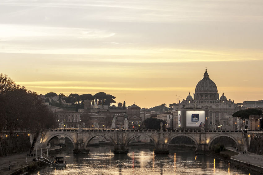 Roma skyline over the Tibre. Reflection Rome Saint Peter's Basilica Skyline Arch Architecture Bridge - Man Made Structure Building Exterior Built Structure City Connection Day Nature No People Outdoors Religion River Rome Italy Sky Spirituality St Peters Basilica Sunset Town Water
