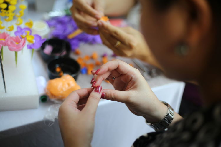Cropped image of woman making crafts at table