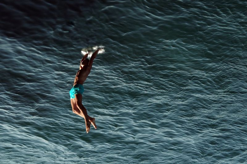 Upside down image of shirtless man diving into sea