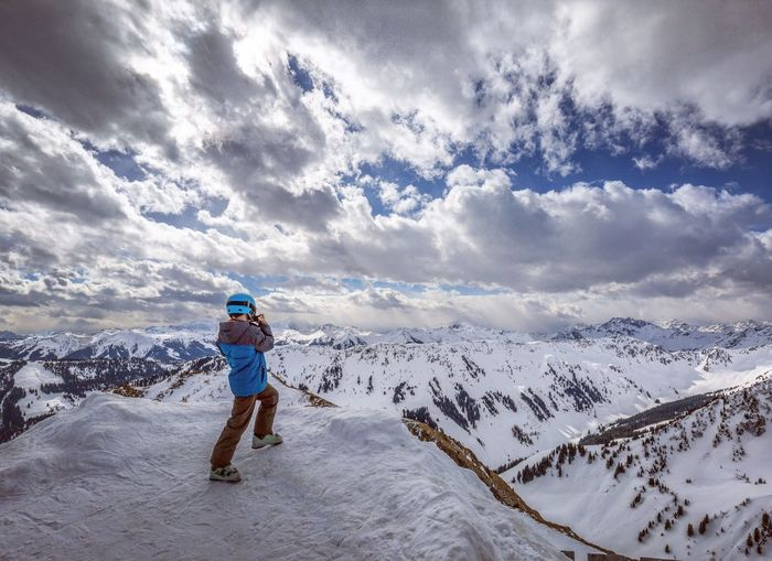 Side view of man standing on snowcapped mountains against cloudy sky