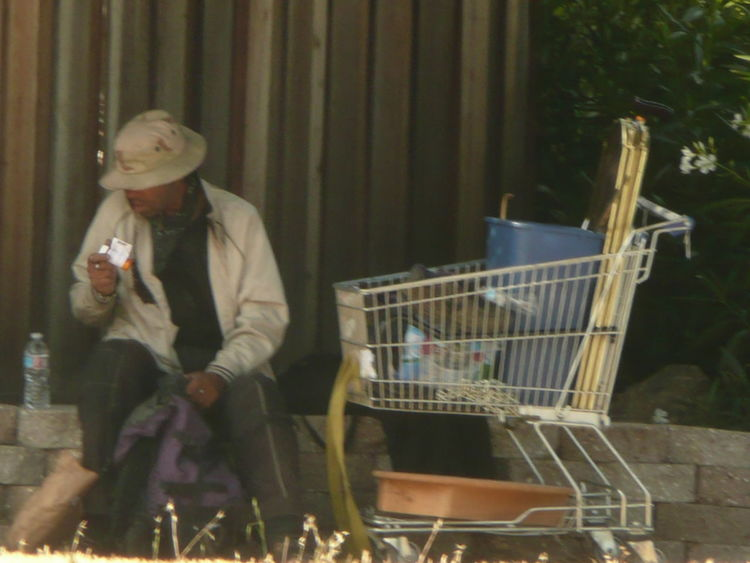 homeless guy sitting with cart Daytime Eating A Meal Hat Lunch Break Sitting Outside Transient Life Bucket Day Food Freshness Full Length Homelessness  Lifestyles One Person Outdoors People Real People Shopping Carts Social Issues Suburban Streets Transient Vagrant Warm Clothing Young Adult Young Women