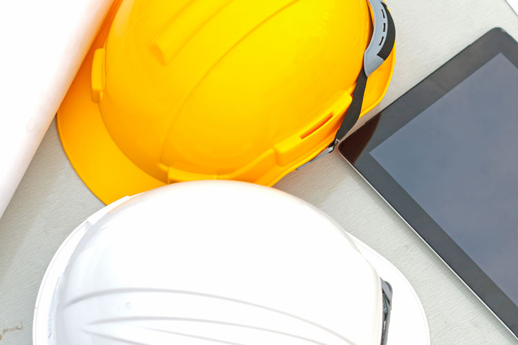 Plan, safety helmet, and tablet on the table Yellow Headwear Indoors  Helmet Hardhat  Close-up No People Hat White Color Protection Low Angle View Industry Orange Color Still Life Balloon Design Construction Industry Equipment Directly Below Construction Equipment Safety